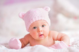 newborn baby girl in pink bear hat and mittens