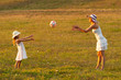 Mother and daughter throwing ball to each other