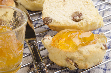 scone spread with butter and orange jam