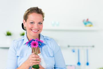 glückliche hausfrau mit blumen