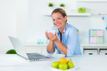 frau entspannt mit laptop in der küche