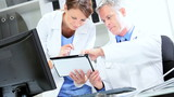 Doctors Checking Patient Information Wireless Tablet