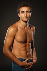 Young muscular male shirtless standing over dark background