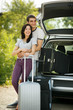 Young couple standing near opened car boot with suitcases