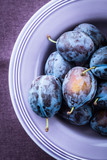 Fresh plums in a purple bowl