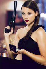 agentin sitzt in der bar mit pistole und schminkspiegel