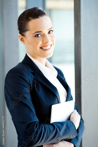 pretty young businesswoman holding tablet computer in office