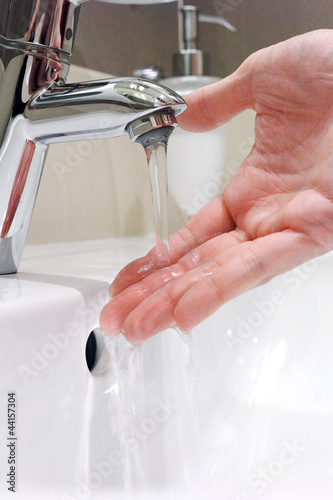 Washing arm  in sink bathroom.
