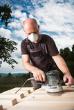 Carpenter sanding a wood with sander with dramatic dark sky poster
