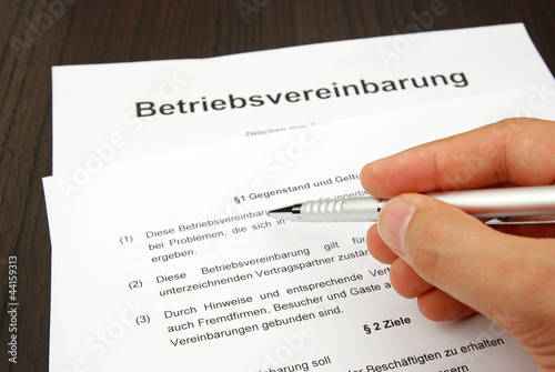 Leinwandbild Motiv Betriebsvereinbarung mit Hand und Kugelschreiber