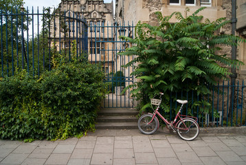 Bicycle parked in front a Trinity College Oxford gate
