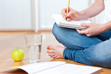 Closeup of young female student sitting on the floor and taking