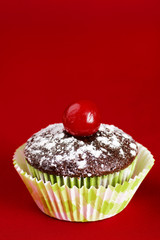 One chocolate cupcake with cherry over red
