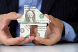 hand holding banknote house icon, real estate concept.