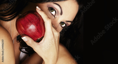 Mysterious woman holding red apple