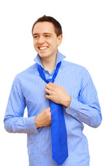 Young business man binding his blue tie