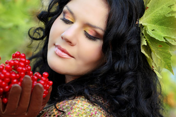Portrait of beautiful Brunette Woman on green leaves with berry
