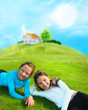 Two young girls laying down on grass and smiling. Beautiful hous
