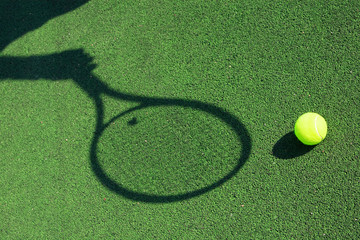 shadow of a tennis racket in hand with a ball