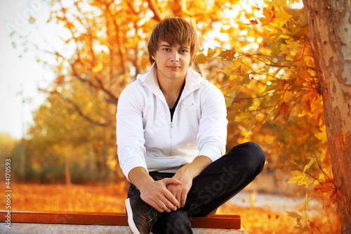 Young man sitting on the bench, autumn