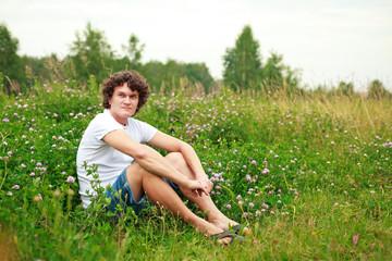 Мужчина сидит на цветущем лугу