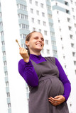 Happy young pregnant woman with key from new apartment