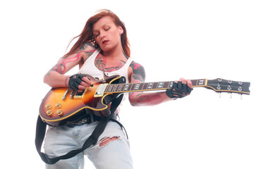 Attractive punk girl with tattoos playing electrical guitar
