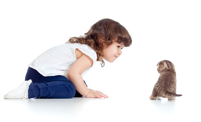 Funny child sitting on floor. Small kitten looking at girl.