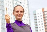 Positive young woman with key from new apartment