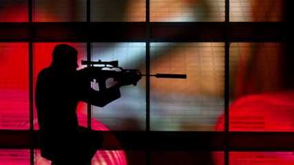 silhouette of a gunman against a colorful background