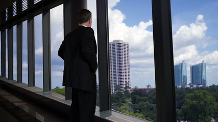 Businessman looks out office windows turns and smiles