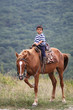 Boy riding horse in Crimea mountains.