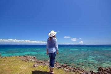 澄んだ珊瑚礁を見渡す女性