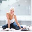 On campus - pretty female student with laptop and books working