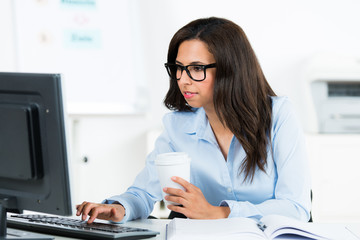 geschäftsfrau schaut interessiert auf ihren computer