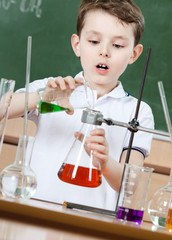 Little chemist pours colored liquid in conical flask