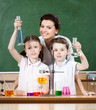 Little pupils study chemistry with their attractive teacher