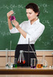 Smiley chemistry teacher examines conical flask with pink liquid