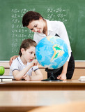 Little schoolboy studies geography with terrestrial globe poster