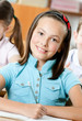 Smiley beautiful schoolgirl sits at the desk