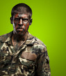 young soldier with camouflage paint looking very serious over gr