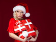 Attractive woman in Christmas cap holds a set of presents