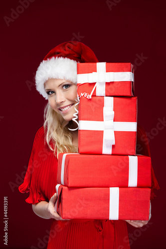 Attractive girl in Christmas cap hands a set of presents