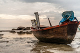 Old boat on beach in overcast sky day poster