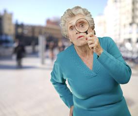 portrait of senior woman looking through a magnifying glass agai