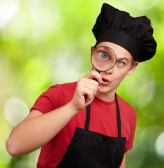 male chef holding magnifying glass