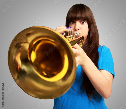 portrait of a young girl blowing trumpet