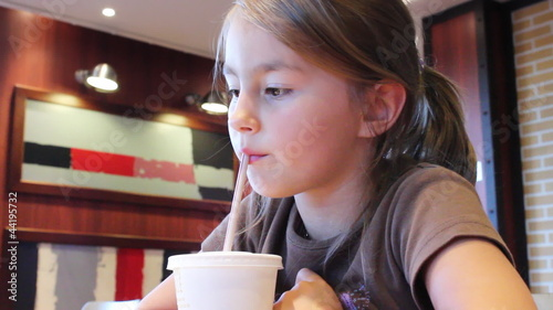 Nice young girl  drinks from plastic cup through straw