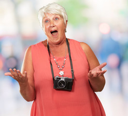 Senior Woman Wearing Camera Shrugging