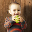 portrait of funny kid holding green apple and smiling against a